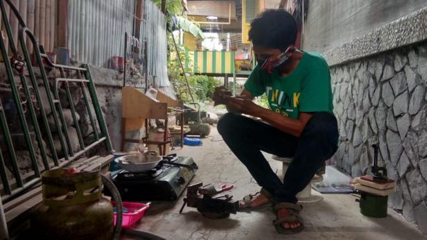 Muhammad Iqbal sedang membuat umpan ikan metal jig untuk dipasarkan