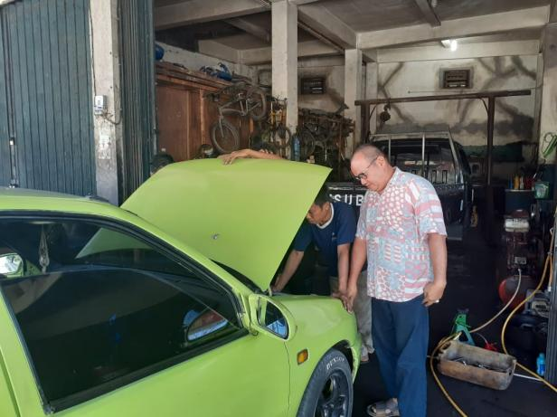 Pilman (kanan) sedang memonitor karyawannya yang tengah memperbaiki mobil pelanggan.