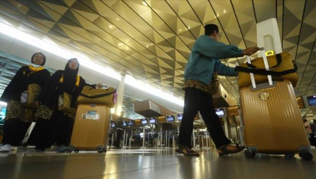 Calon Jamaah Umroh tertidur saat menunggu kepastian pemberangkatan ke Tanah Suci Mekah di Terminal 3 Bandara Soekarno Hatta, Tangerang, Banten, Kamis (27/2) (Suara.com)