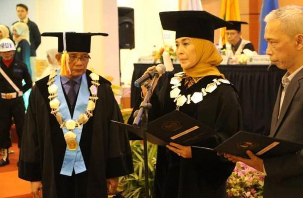 Diana Kartika saat melakukan pemberian ijazah pada saat wisuda Ketua BEM UBH Padang