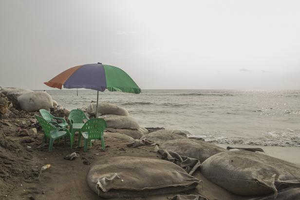 Tenda dan bangku plastik yang ditinggal di pinggir pantai