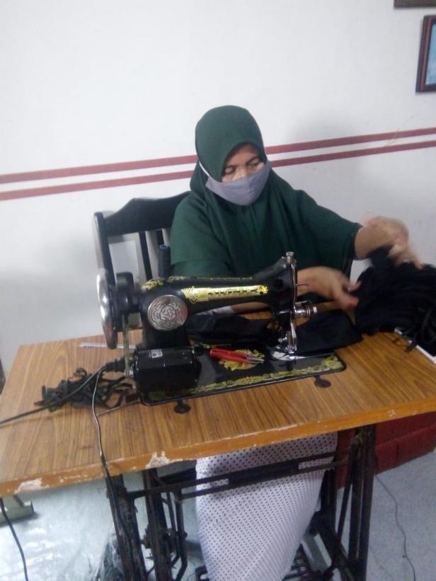 Seorang oenjahit masker di Gang Melayu