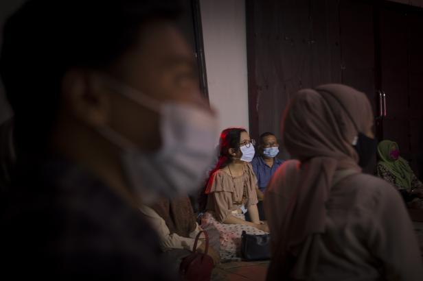 Penonton mengenakan masker