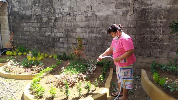 Keluarga pasien yang menginap di Rumah Singgah Yayasan Semen Padang tengah menyiram tanaman yang terletak di taman belakang