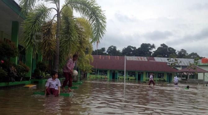 Siswa di MIN 3 Padang bermain di genangan air yang ada di sekolah mereka.