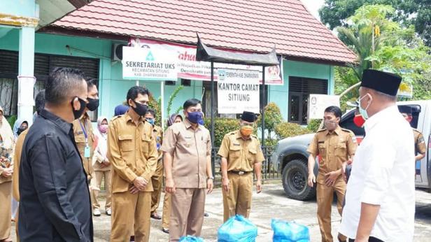 Bupati Dharmasraya Sutan Riska Tuanku Kerajaan menyerahkan bantuan masker kepada masyarakat yang diterima lansung wali nagari.