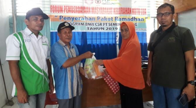 Ketua Forum Pemberdayaan Masyarakat Kelurahan Koto Lua, Zainal (dua dari kiri) didampingi sejumlah pengurus forum, menyerahkan bantuan paket sembako ramadan kepada salah seorang warga Koto Lua.