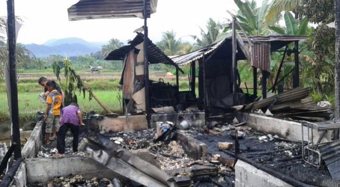 Sejumlah anak- anak melihat kondisi puing-puing rumah semi permanen yang terbakar di Baringin