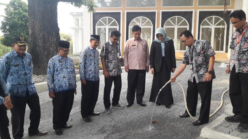 Kadis PUPR Kota Padang, Yenni Yuliza, menyaksikan proses penyerapan air oleh porous concrte di areal parkir Club House PT Semen Padang