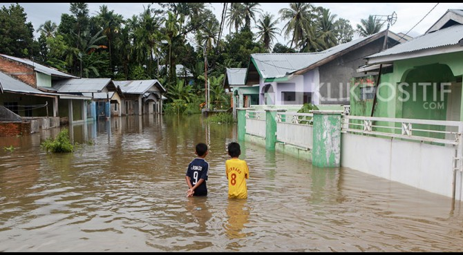 Dua orang anak sedang berdiri ditengah banjir (ilustrasi)