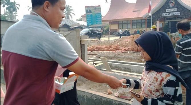 Camat Harau Andri Yasmen saat membagikan masker kepada masyarakat yang berkegiatan di luar rumah.