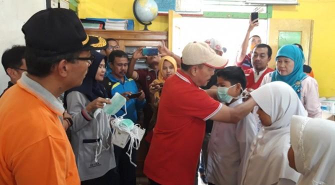 Wabup Zuldafri Darma memasangkan masker kepada siswa SD.