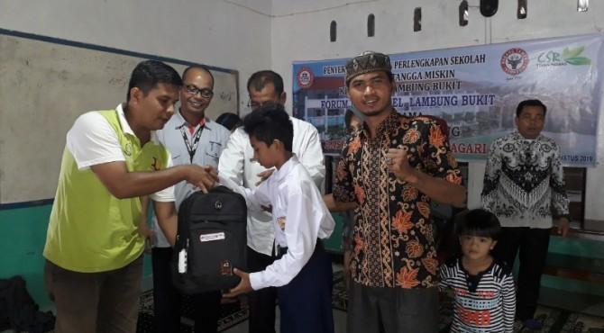Sekretaris Forum Pemberdayaan Masyarakat Lambung Bukit, Boni Ikhlas, menyerahkan secara simbolis bantuan pendidikan