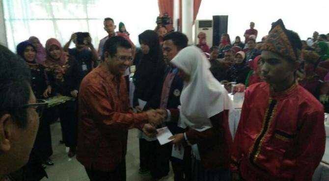 Dirut PT Semen Padang, Benny Wendry, memberikan selamat kepada salah seorang pelajar yang menerima bantuan pendidikan di Limapuluh Kota