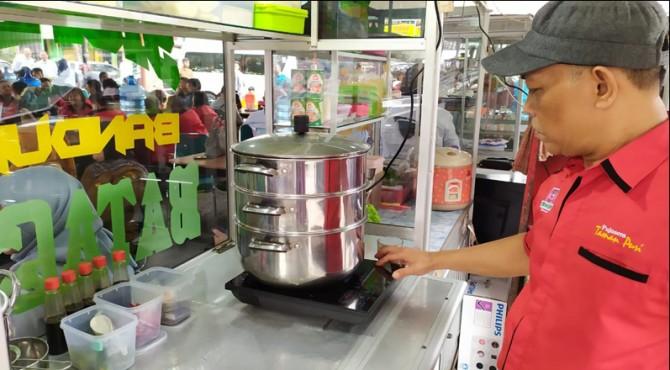 Salah satu pedagang menggunakan kompor listrik saat akan memasak