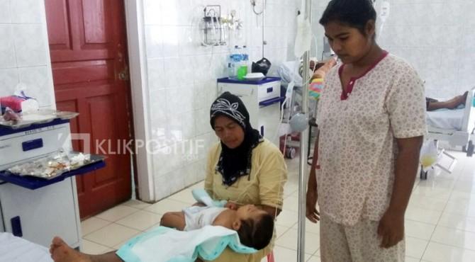 Reza terbaring di pangkuan neneknya dan ditemani ibunya saat dalam perawatan di RSUP DR M Djamil Padang.