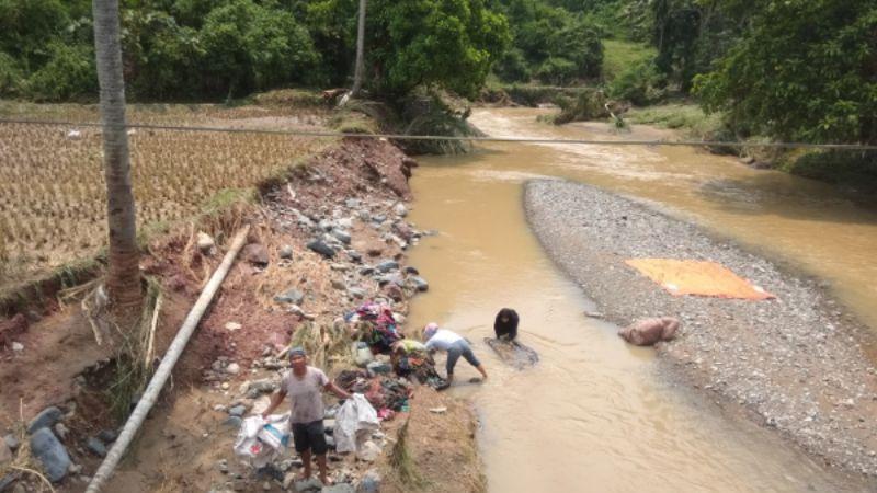Warga Talago Gunuang Saat Membersihkan Pakaian yang Direndam Banjir