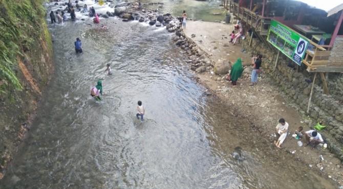 Tampak pengunjung dari atas jembatan Batang Tiku tengah menikmati kesegaran aliran Batang Tiku.