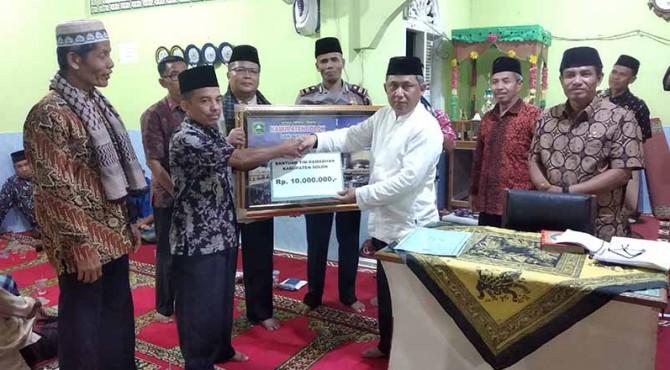 Asisten Bidang Ekbangkesra, Aliber Mulyadi bersama Kapolsek X Koto Diateh, Iptu Hendri menyerahkan bantuan kepada pengurus masjid.