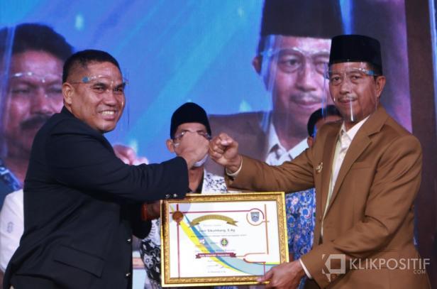 Wakil Bupati Pasaman Barat Risnawanto dalam acara IMTC memberikan penghargaan kepada wartawan pemerhati pendidikan Junir Sikumbang