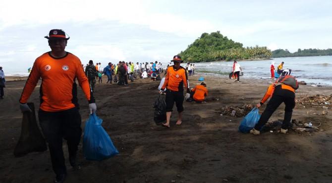 Salah seorang anggota TRC Semen Padang membawa kantong plastik berisikan sampah yang dikumpulkan dari bibir Pantai Air Manis