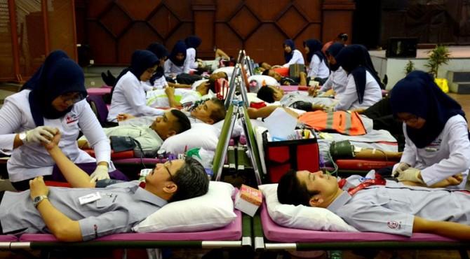 Direktur keuangan PT Semen Padang Tri Hartono Rianto (kiri) tengah mendonorkan darahnya kepada petugas PMI Kota Padang di Gedung Serba Guna Semen Padang, Kamis, 11 Agustus 2016