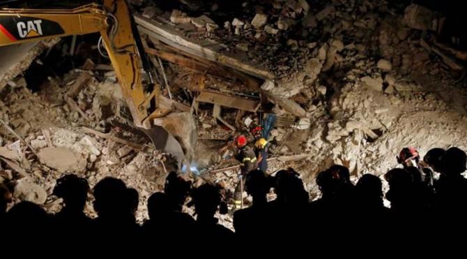 Penyelamat bekerja di malam hari di sebuah rumah runtuh menyusul gempa bumi di Pescara del Tronto, Italia tengah, 24 Agustus 2016.