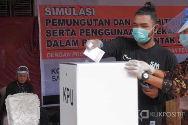 Seorang pemilih memasukan surat suara ke kotak suara