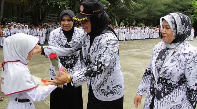 Seorang siswa memberikan bunga kepada guru saat Peringatan Hari Pendidikan Nasional