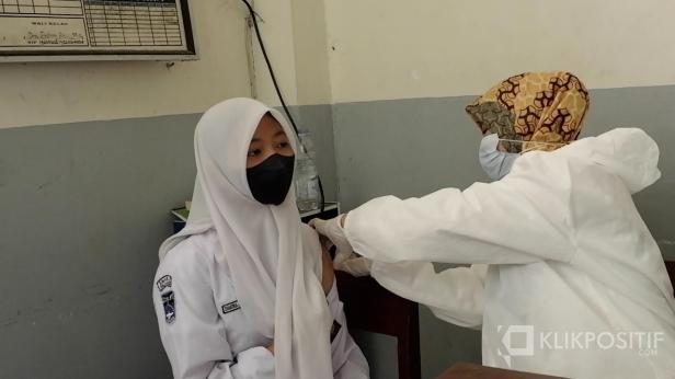 Seorang siswa melakukan vaksinasi
