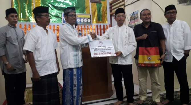 Direktur Keuangan PT Semen Padang, Tri Hartono Rianto (tiga dari kiri) menyerahkan tanda mata kepada penguris Musala Al Ikhlas sebagai tanda kunjungan Tim Safari Ramadan Semen Padang.
