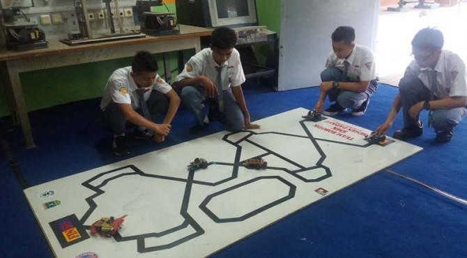 Sejumlah siswa SMK Semen Padang jurusan Elekronika Industri tengah melihat kemampuan robot Line Flowwer berjalan di atas jaur berwarna hitam.