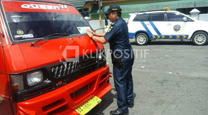 Petugas Dinas Perhubungan Padang Pariaman saat menempelkan stiker tanda telah dilakukan pengujian kelayakan kendaraan di Kantor Dinas Perhubungan