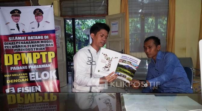 Kepala DPMPTP Hendra Aswara menunjukan Buku Jendela Investasi Padang Pariaman kepada masyarakat yang mengurus izin usaha di Kantornya.