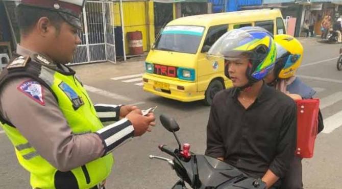 Polisi sedang memeriksa kelengkapan surat kendaraan dalam Operasi Patuh 2019.
