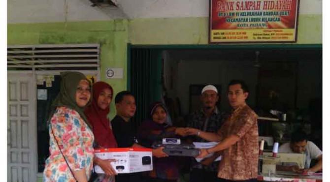 Staf Bidang Pendidikan Kesehatan Sosial dan Lingkungan Hidup Biro CSR PT Semen Padang, Yumendri (Kanan) menyerahkan bantuan ke Bank Sampah Hidayah Bandar Buat