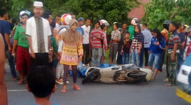 Warga mengerumuni jenazah korban kecelakaan di jalan menjelang petugas polisi mengevakuasi.