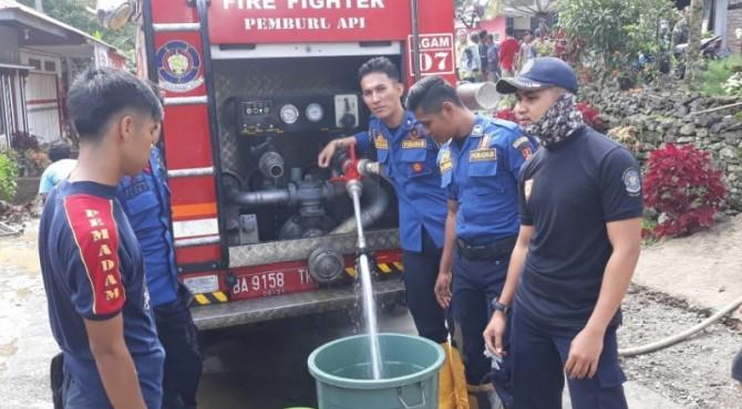 Personel Rescue Damkar Agam menyalurkan air bersih