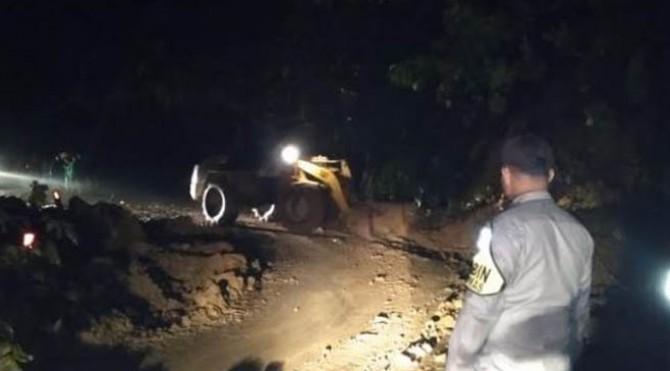 petugas berupaya membersihkan materil yang menutupi badan jalan