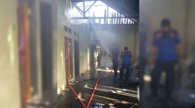 Petugas damkar melakukan proses pendinginan di rumah warga yang terbakar