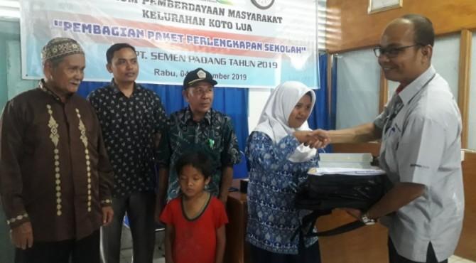 Staf Bina Lingkungan CSR PT Semen Padang Subrianto (kanan)  menyerahkan bantuan paket pendudikan kepada pelajar kurang mampu.