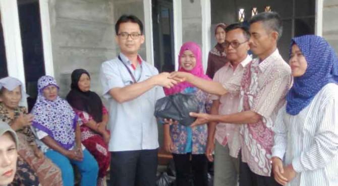 Staf Bidang Pendidikan Kesehatan Sosial dan Lingkungan Hidup Biro CSR PT Semen Padang, Alfred Rusly (tengah) menyerahkan paket sembako secara simbolis kepada warga Limau Manis Selatan
