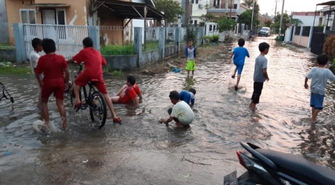 Sejumlah anak-anak di Kompleks Permata Surau Gadang tengah bermain si genangan air yang meluap di badan jalan kompleks