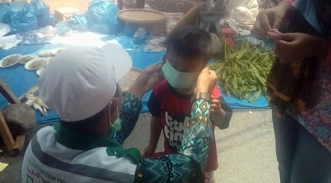 Anggota FPI Tanah Datar memasangkan masker kepada anak-anak