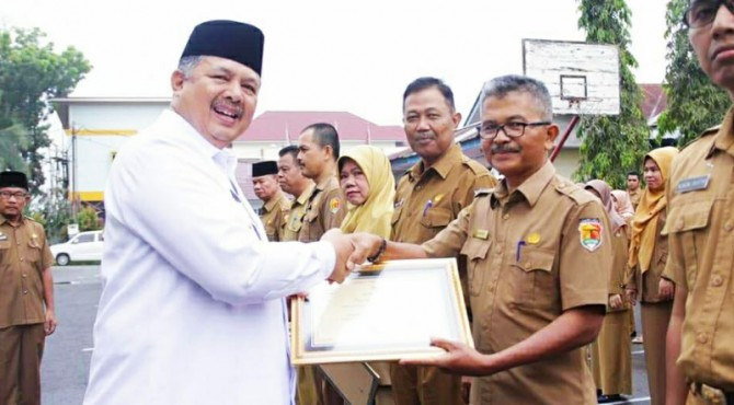 Wako Solok Zul Elfian menyerahkan penghargaan kepada Kabag Humas Nurzal Gustim.