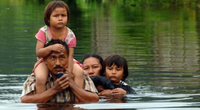 Warga mengevakuasi keluarganya melewati banjir yang merendam kawasan Batipuhpanjang, Kototangah, Padang, Sumatera Barat, Selasa (22/3). Hujan sejak Selasa (22/3) dini hari menyebabkan sungai meluap dan banjir merendam ratusan rumah di kota itu serta memutus akses jalan utama.