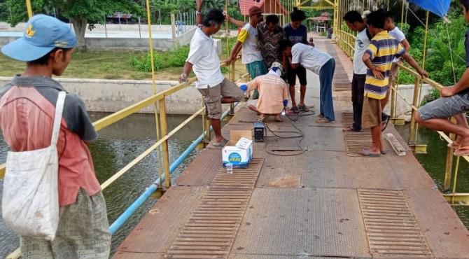 Perbaikan jembatan oleh warga