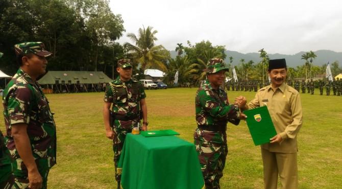 Dandim 0309/Solok Menyerahkan Naskah Kegiatan TMMD ke 106 kepada Bupati Solok Selatan Muzni Zakaria disaksikan Danlantamal II Padang, Laksamana Pertama TNI Dafit Santoso, saat upacara penutupan TMMD tersebut di Bidar Alam, Kamis (31/10)