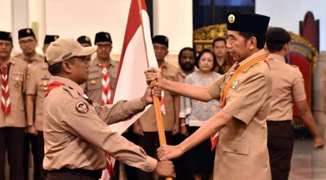 Presiden Jokowi menyerahkan bendera Merah Putih kepada ketua kontingan saar melepas delegasi Pramuka Indonesia pada Jambore Pramuka Dunia, di Istana Negara, Jakarta, Jumat (19/7)