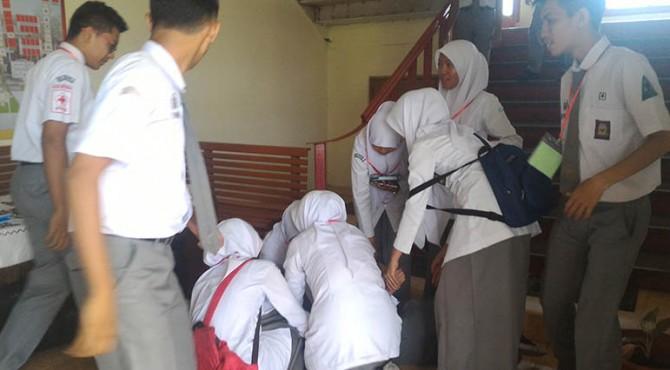Sejumlah siswa menolong Nadra setelah jatuh pingsan seusai mengikuti UN sesi pertama, Senin (04/04/2016)